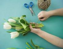 Mains du ` s d'enfants avec un bouquet de vue supérieure de tulipes Fond pour une carte d'invitation ou une félicitation La fille Photographie stock