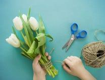 Mains du ` s d'enfants avec un bouquet de vue supérieure de tulipes Fond pour une carte d'invitation ou une félicitation La fille Photo libre de droits