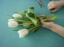 Mains du ` s d'enfants avec un bouquet de vue supérieure de tulipes Fond pour une carte d'invitation ou une félicitation La fille Photos stock