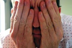 Mains du ` s d'homme devant son visage images stock