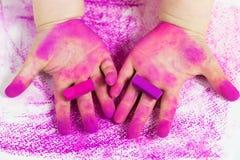 Mains du ` s de bébé avec les craies en pastel roses Photographie stock