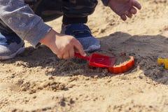 Mains du ` s de bébé dans le sable, bébé jouant dans le sable Images libres de droits