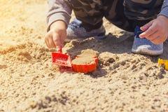 Mains du ` s de bébé dans le sable, bébé jouant dans le sable Photos stock