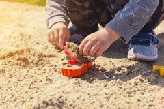 Mains du ` s de bébé dans le sable, bébé jouant dans le sable Photographie stock