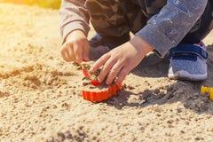 Mains du ` s de bébé dans le sable, bébé jouant dans le sable Photo libre de droits