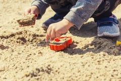 Mains du ` s de bébé dans le sable, bébé jouant dans le sable Photographie stock libre de droits