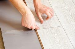 Mains du ` s de bricoleur établissant les panneaux de plancher en stratifié Photographie stock libre de droits