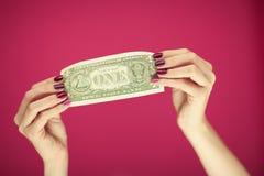 Mains du ` s de femme avec le vernis à ongles rose parfait et beau tenant une note du dollar Photographie stock libre de droits