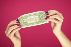 Mains du ` s de femme avec le vernis à ongles rose parfait et beau tenant une note du dollar Photos libres de droits