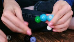 Mains du ` s de femme de plan rapproché établissant des modèles de molécule d'ensemble en plastique coloré de construction banque de vidéos