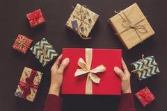 Mains du ` s de femme tenant le boîte-cadeau Le présent enferme dans une boîte le fond images libres de droits