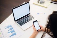 Mains du ` s de femme utilisant le téléphone portable et l'ordinateur portable au bureau Photo stock