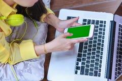 Mains du ` s de femme utilisant le téléphone portable et l'ordinateur portable sur le bois de plancher photographie stock