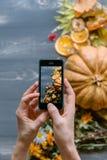 Mains du ` s de fille avec le téléphone, la composition en photographies avec le thé et le fruit Image stock