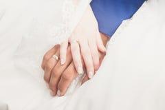Mains du ` s de jeunes mariés avec des anneaux de mariage Image stock
