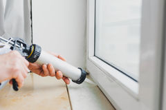 Mains du travailleur à l'aide d'un tube de silicone pour la réparation de la fenêtre Image libre de droits