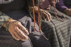 Mains du vieux passionné bouddhiste tenant des perles de prière Photos stock