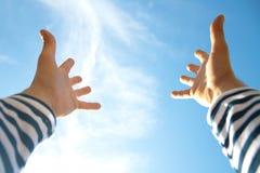 Mains en air à travers le ciel bleu Photographie stock