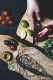 Mains en cours de faire cuire des poissons, poivre, persil, tomate, chaux sur une planche à découper sur un vert en bois noir de  photo stock