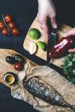 Mains en cours de faire cuire des poissons, poivre, persil, tomate, chaux sur une planche à découper sur une vue supérieure de fo photographie stock libre de droits