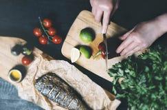 Mains en cours de faire cuire des poissons, poivre, persil, tomate, chaux sur une planche à découper sur une vue supérieure de fo image stock