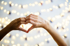 Mains en forme de coeur avec des lumières de décoration comme fond Image stock