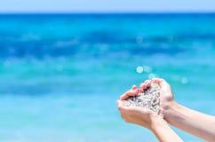 Mains en gros plan avec le sable dans la forme du coeur contre la mer tropicale de turquoise Image libre de droits