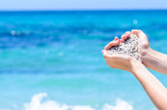 Mains en gros plan avec le sable dans la forme du coeur contre la mer tropicale de turquoise Photo libre de droits