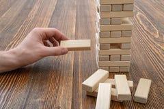 Mains en gros plan de l'homme jouant avec les briques en bois Images stock