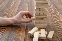 Mains en gros plan de l'homme jouant avec les briques en bois Photos stock