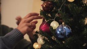 Mains en gros plan des couples heureux décorant l'arbre de Noël dans la chambre avant des vacances An neuf et temps de No?l banque de vidéos