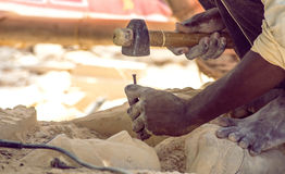 Mains en pierre de travailleur découpant la pierre Image libre de droits
