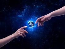 Mains en terre émouvante de planète de l'espace Images stock