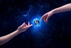 Mains en terre émouvante de planète de l'espace Photos stock