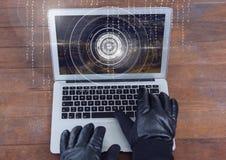 Mains enfilées de gants dactylographiant sur un ordinateur portable sur une table en bois Photos libres de droits