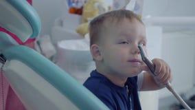 Mains enfilées de gants de dentiste vérifiant les tooths du petit garçon insouciant s'asseyant dans la chaise lui montrant un pla banque de vidéos