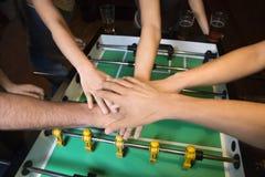 Mains ensemble au-dessus de la table du football. images stock