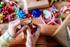 Mains enveloppant des cadeaux de Noël Photos stock