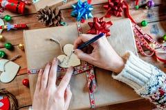 Mains enveloppant des cadeaux de Noël Photos libres de droits