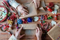 Mains enveloppant des cadeaux de Noël Photo libre de droits