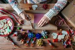 Mains enveloppant des cadeaux de Noël Image libre de droits