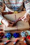 Mains enveloppant des cadeaux de Noël Photo stock