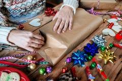 Mains enveloppant le cadeau de Noël Photographie stock