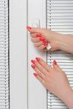 Mains et abat-jour femelles à la fenêtre Photographie stock