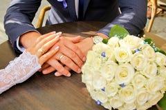 Mains et anneaux bouquet blanc de mariage sur la table en bois Photographie stock