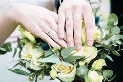 Mains et anneaux de jeunes mariés sur le bouquet de mariage Images stock