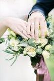 Mains et anneaux de jeunes mariés sur le bouquet de mariage Photos libres de droits
