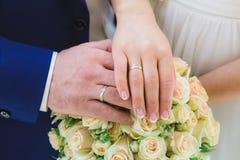 Mains et anneaux de jeunes mariés sur le bouquet de mariage Image libre de droits