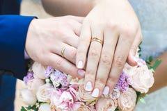 Mains et anneaux de jeunes mariés sur le bouquet de mariage Photographie stock libre de droits