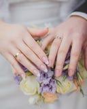 Mains et anneaux sur le bouquet de mariage Photo libre de droits
